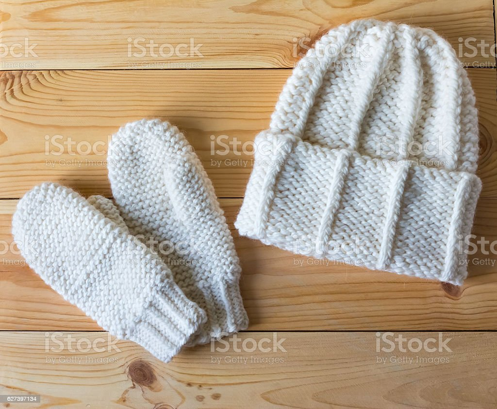 Hat and mittens connected by hand from wool stock photo