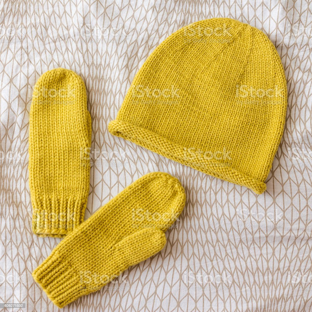 Hat and mittens connected by hand from wool yellow stock photo
