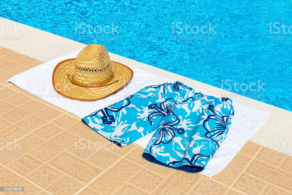 Hat and swimming trunks on towel near swimming pool stock photo