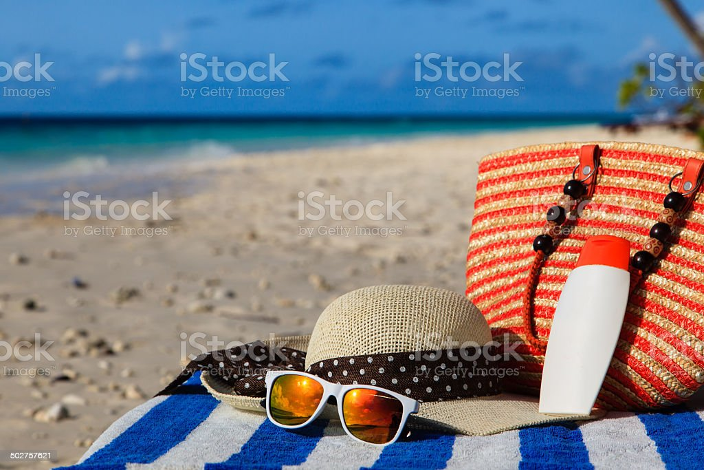 hat, bag, sun glasses on tropical beach stock photo
