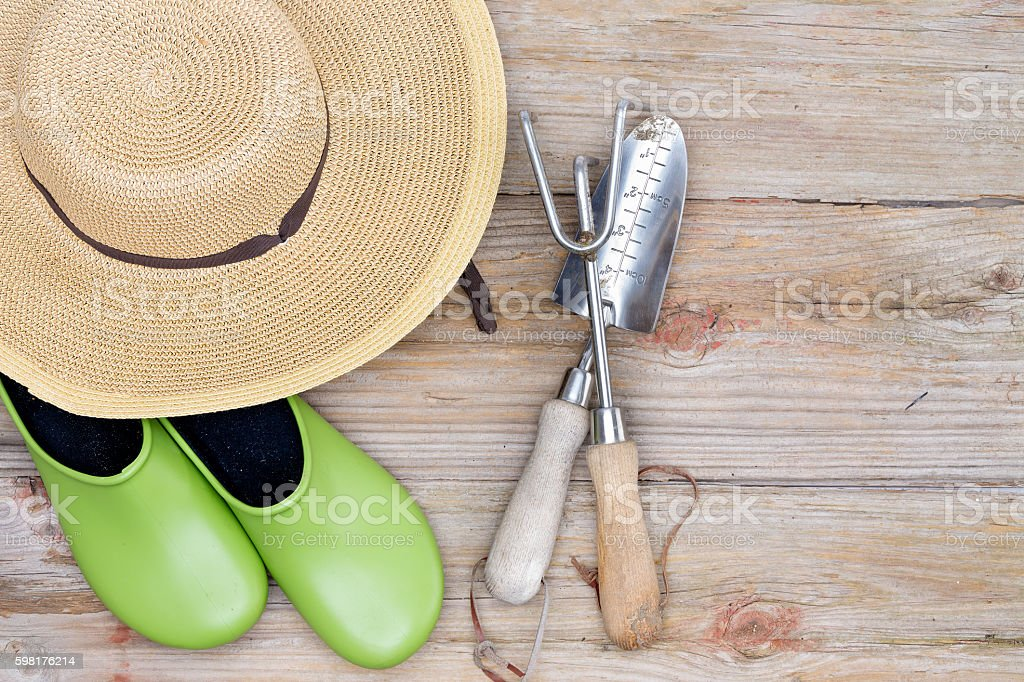 Hat, Gardening Shoes and Tools on Wood Background stock photo
