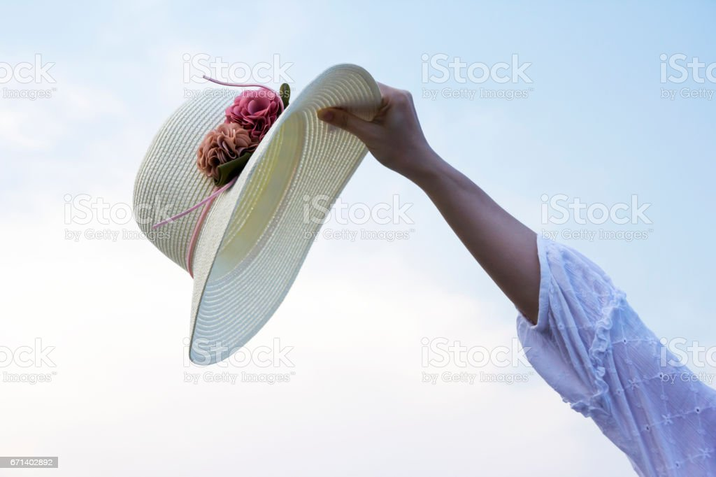 Hat in hand woman on the beach stock photo