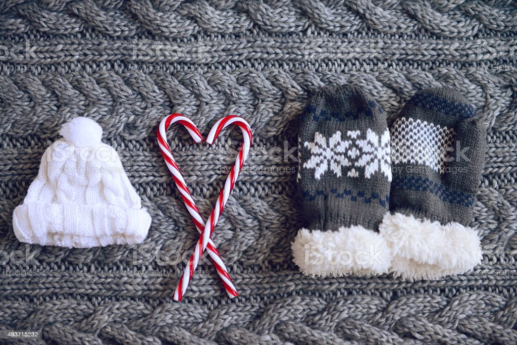 hat, mittens and Christmas candies on a woolen background stock photo