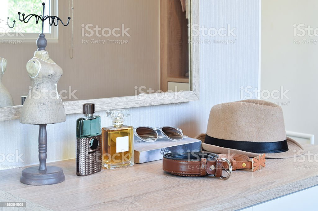 hat ,perfume and leather belt on a wooden dressing table stock photo
