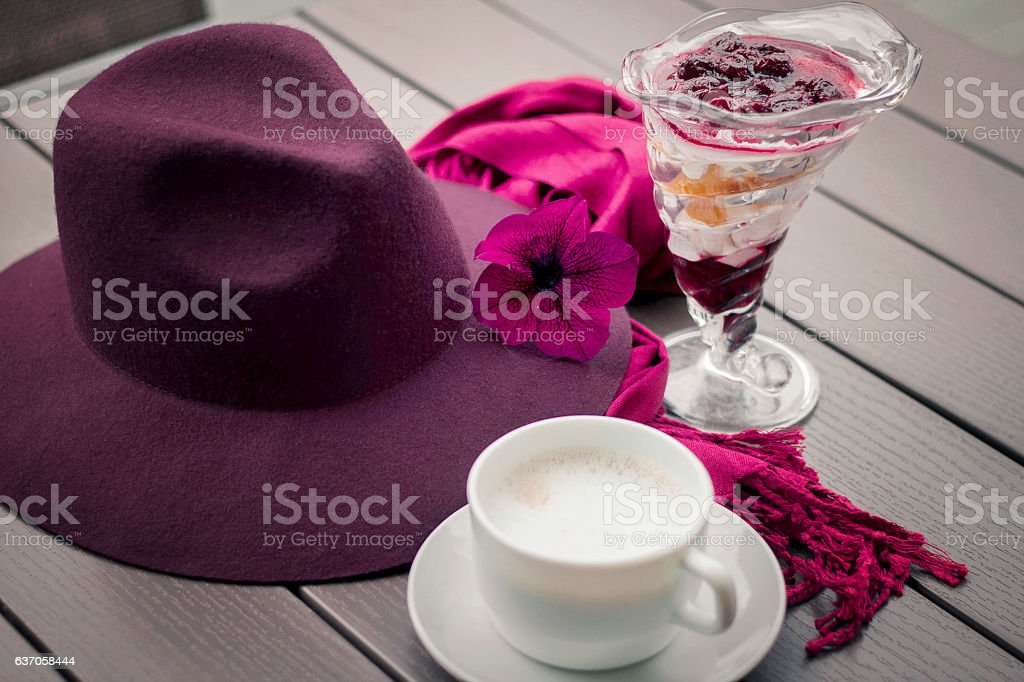 hat with cup of coffee on wooden table stock photo