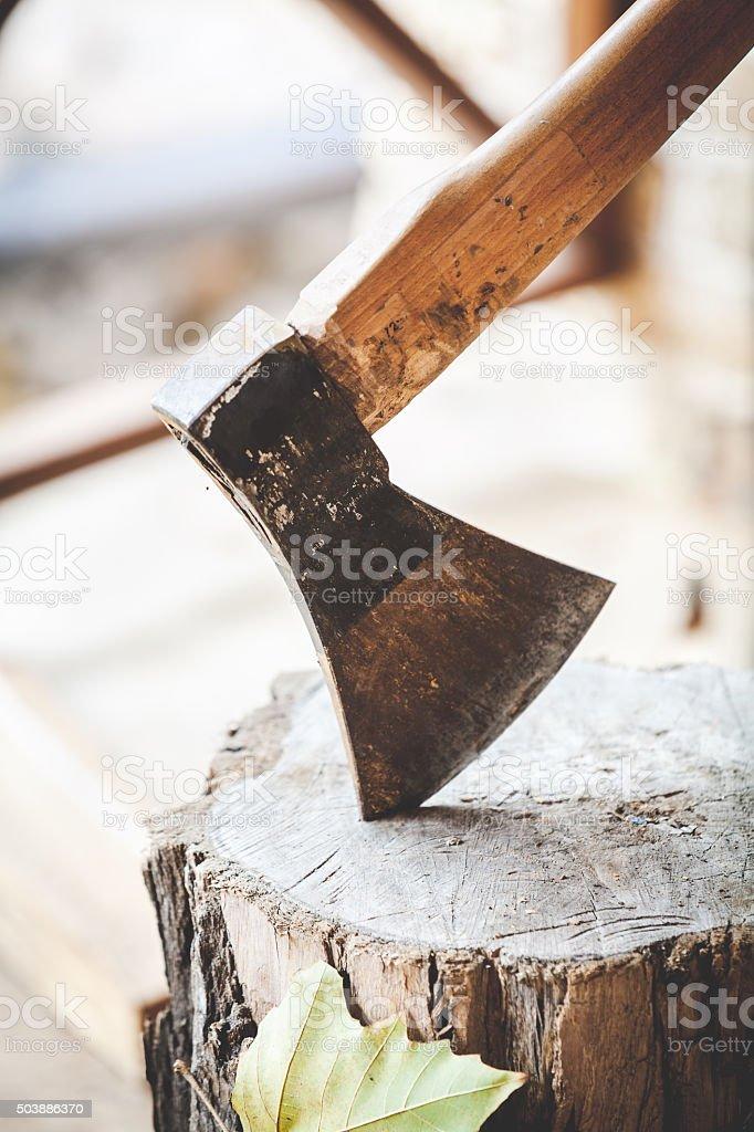 Hatchet sticking in stump close-up stock photo