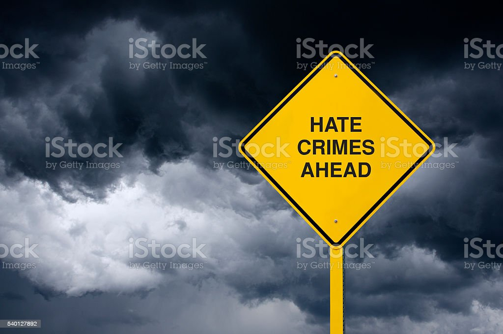 Hate Crimes Ahead Road Sign in Front of Storm Clouds stock photo
