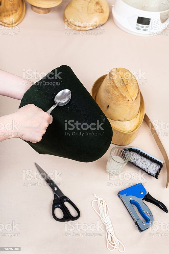 hatter applies an adhesive a felt hood for fixing stock photo