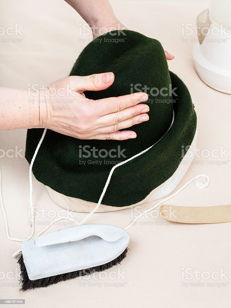hatter fixes a felt hood on dummy for shaping stock photo