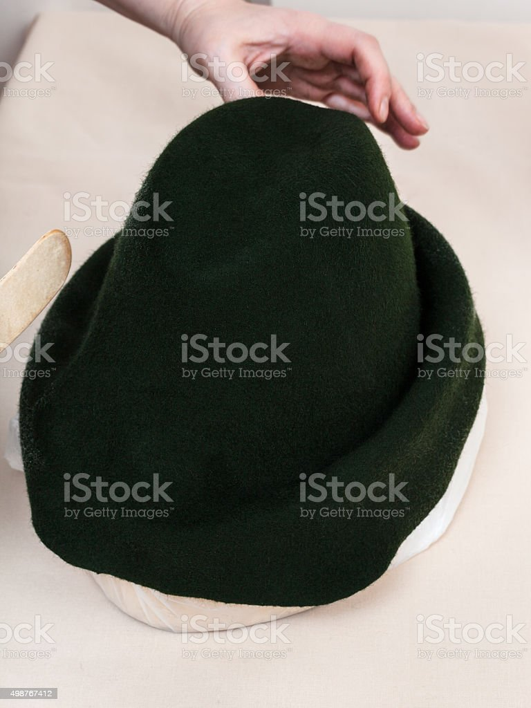 hatter fixes a felt hood on hat-block for shaping stock photo
