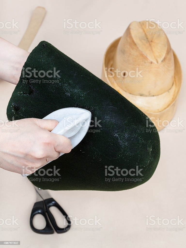 hatter gluing a felt hood for shaping on dummy stock photo