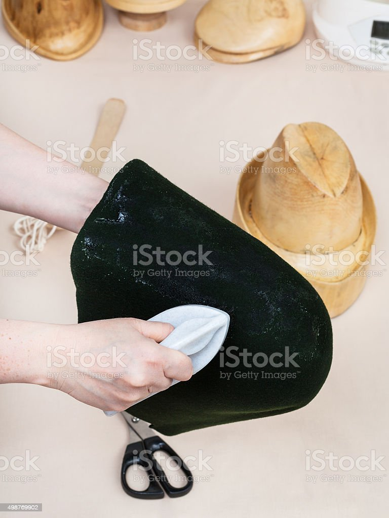 hatter gluing a felt hood for shaping on hat-block stock photo