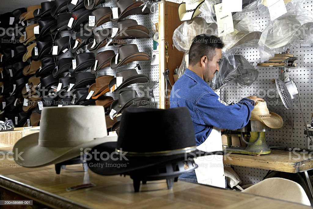 Hatter shaping stetson in workshop, rear view stock photo