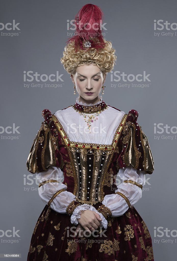 Haughty queen in royal dress isolated on grey stock photo