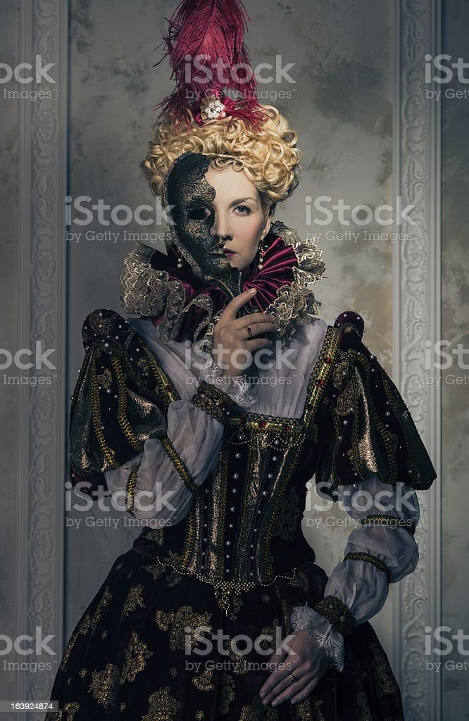 Haughty queen in royal dress with mask stock photo