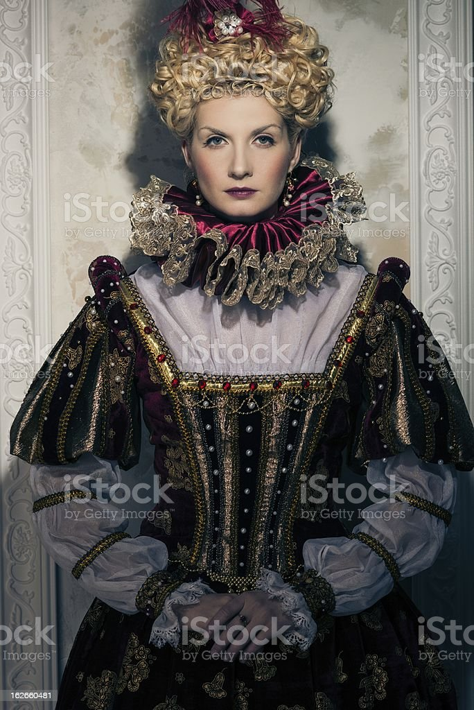 Haughty-looking queen in royal dress including neck ruffle stock photo