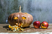Haunted carved pumpkins for Halloween with apple
