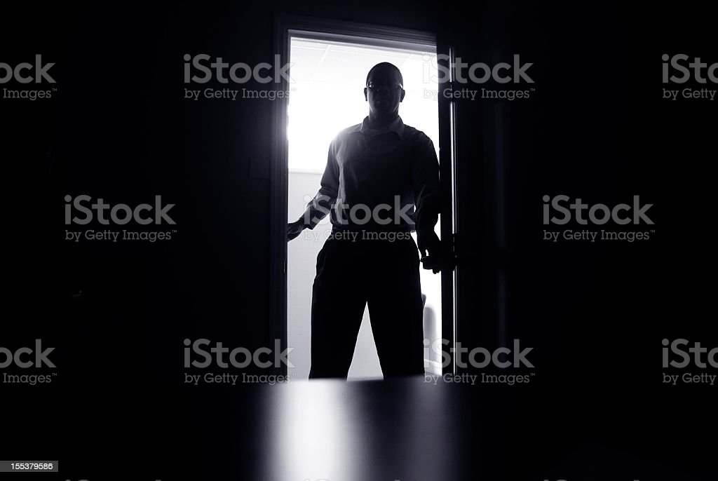 haunting office scene; man in doorway silhouetted stock photo