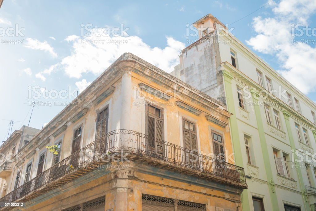 This is a horizontal, color photograph of a corner building with a...