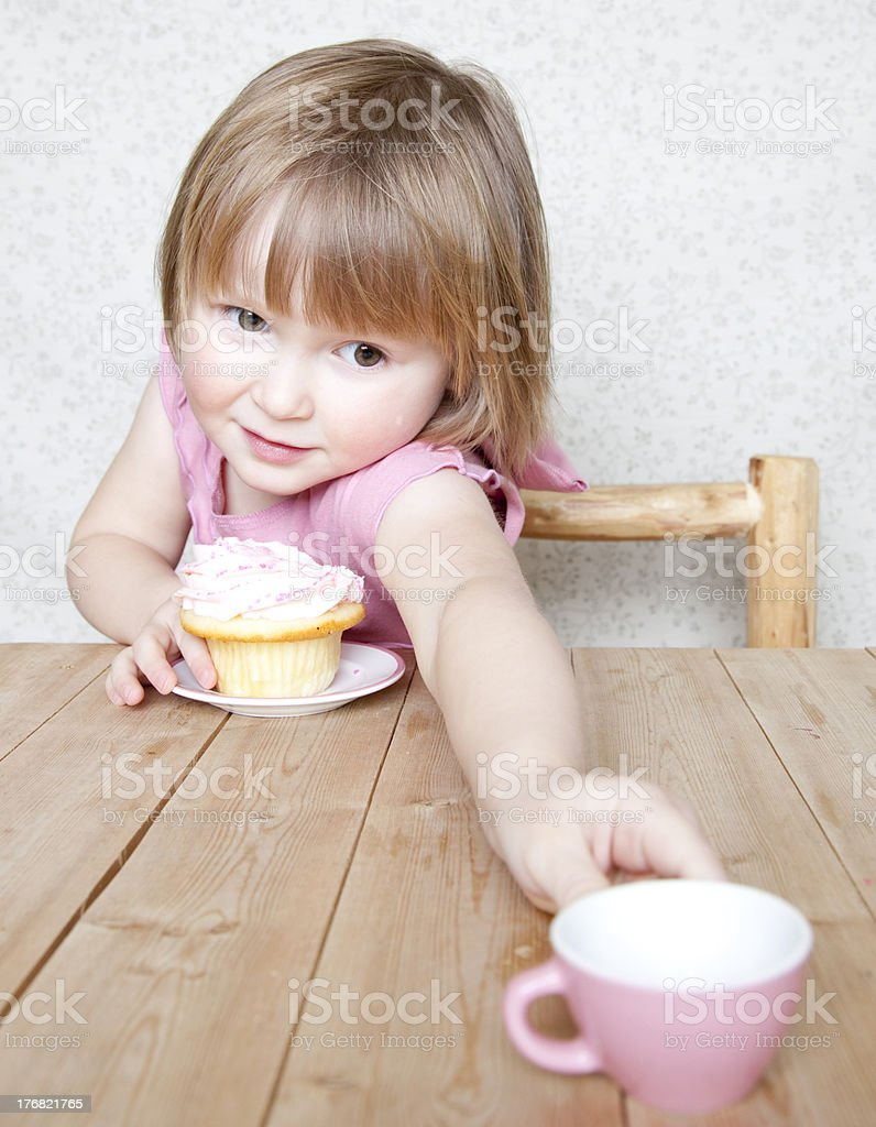 Have some tea - Little girl with cupcake and cup royalty-free stock photo