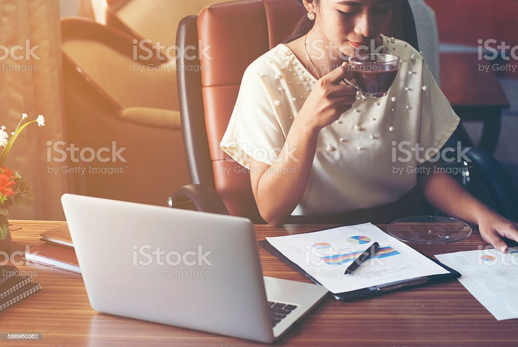 Having coffee while she preparing paper works. stock photo