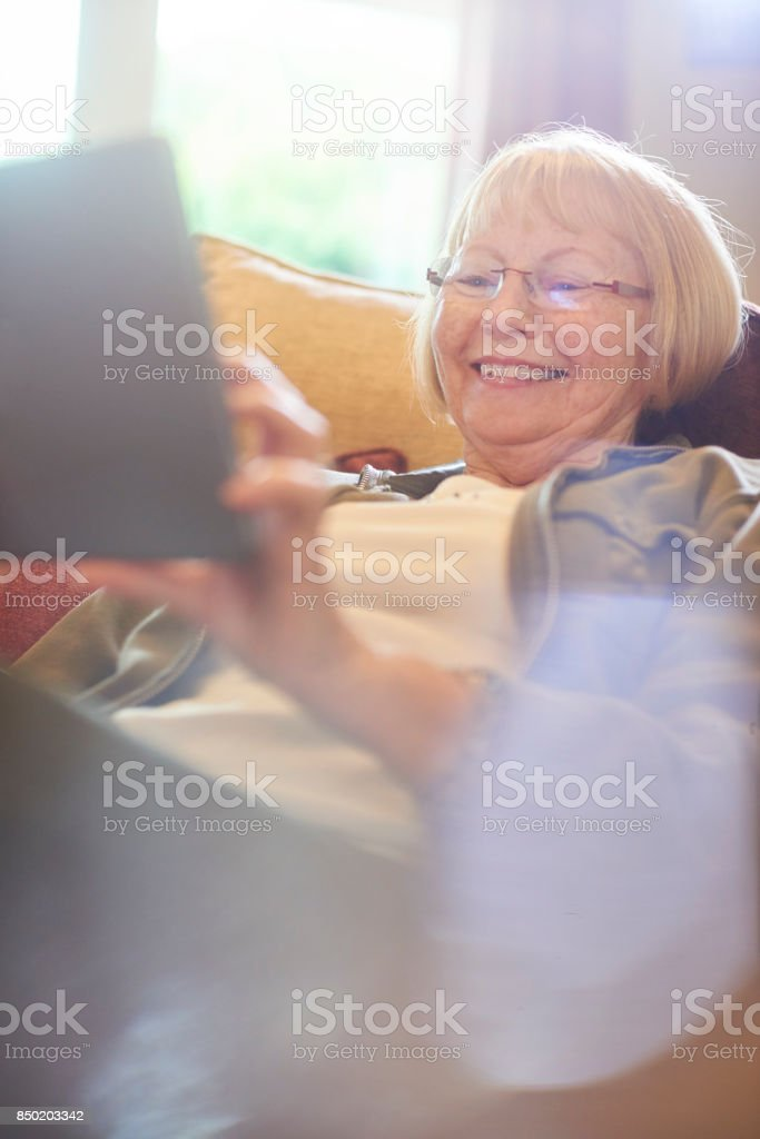 having fun on her digital tablet stock photo