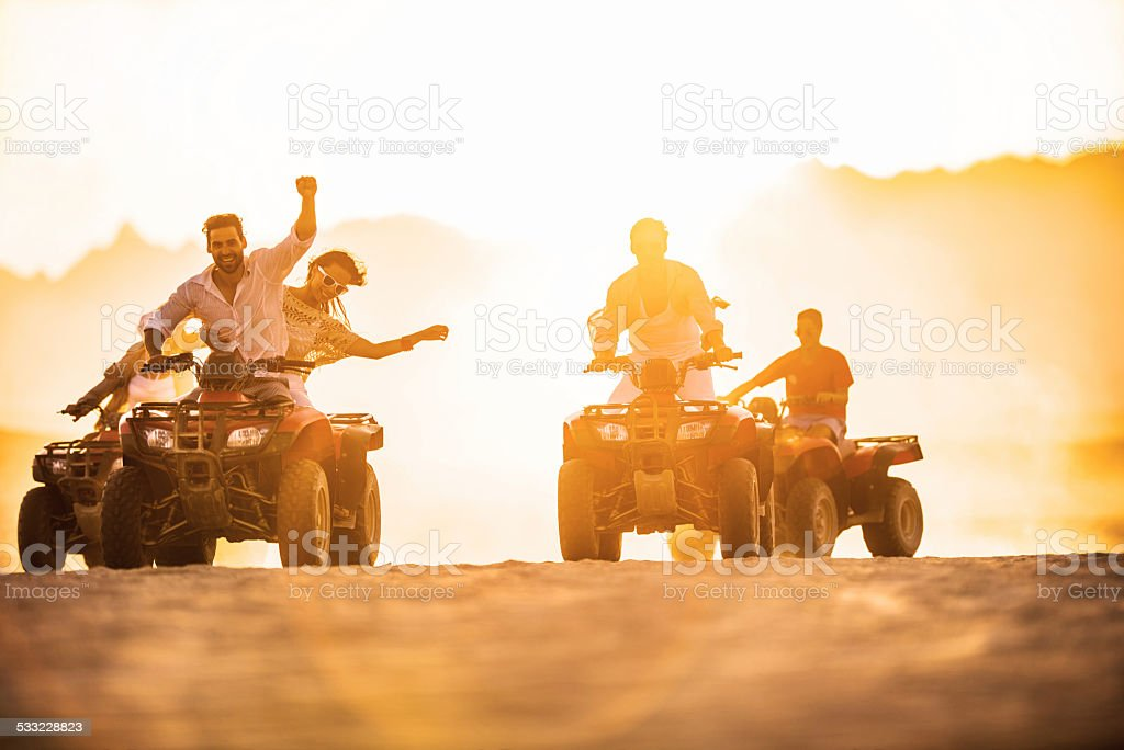 Having fun on quad bikes at sunset. stock photo