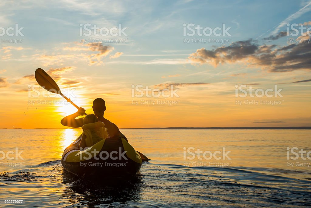 Having Fun Sea Kayaking At Sunset stock photo