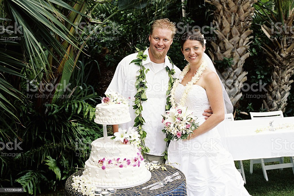 Hawaii style wedding couple and cake cutting stock photo