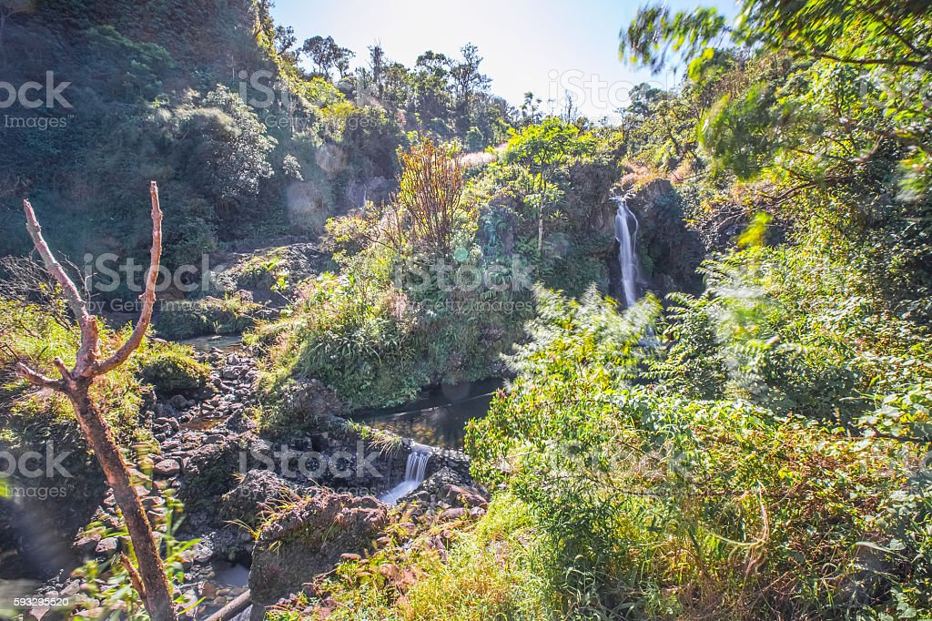 Hawaii waterfall with rocks and lush trees stock photo