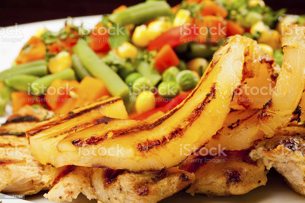Hawaiian chicken served with mexican salad and pineapple stock photo