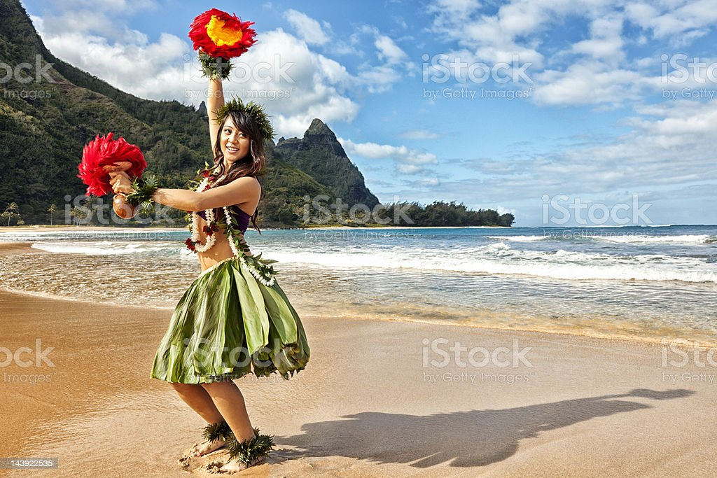 Hawaiian Hula Dancer on Beach with Red Feather Shakers stock photo