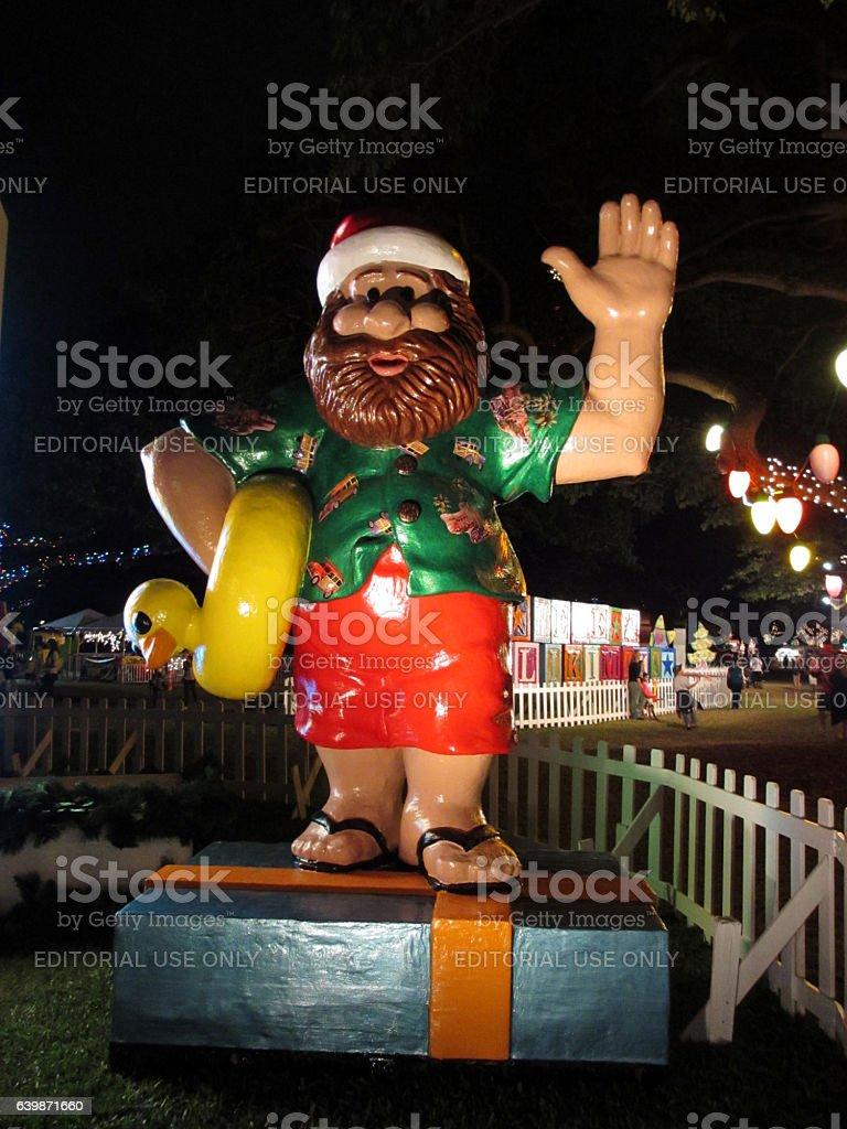 Hawaiian Santa Figures holds rubber ducky as he waves stock photo