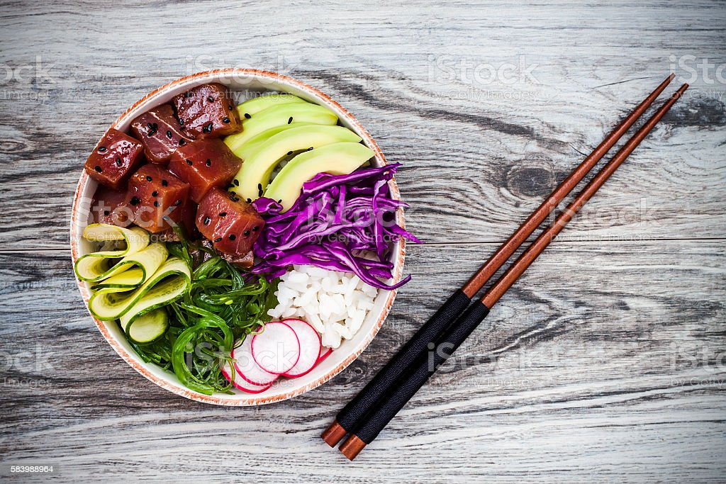 Hawaiian tuna poke bowl with seaweed, avocado, red cabbage, radishes stock photo