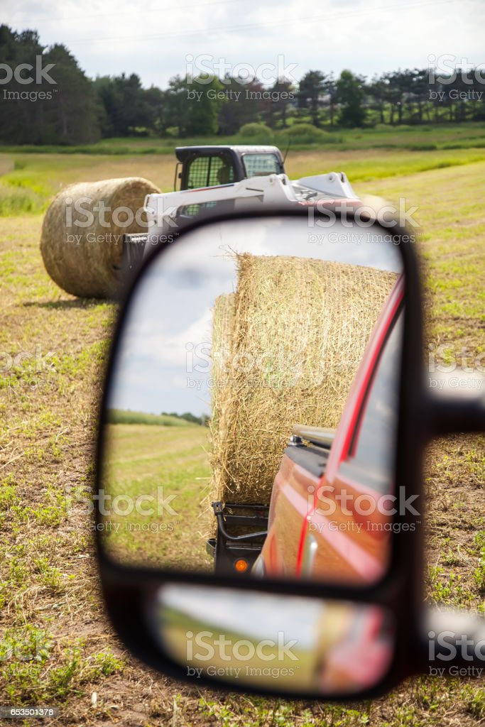Hay Bales on Trailer in Mirror, Skid Loader in Field stock photo