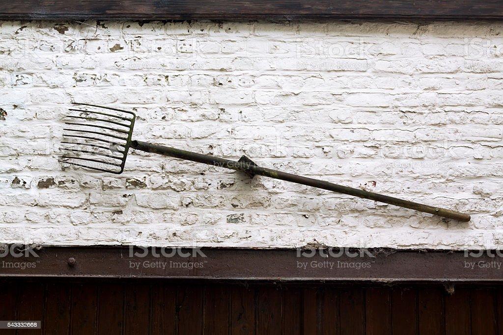 Hay fork at wall stock photo