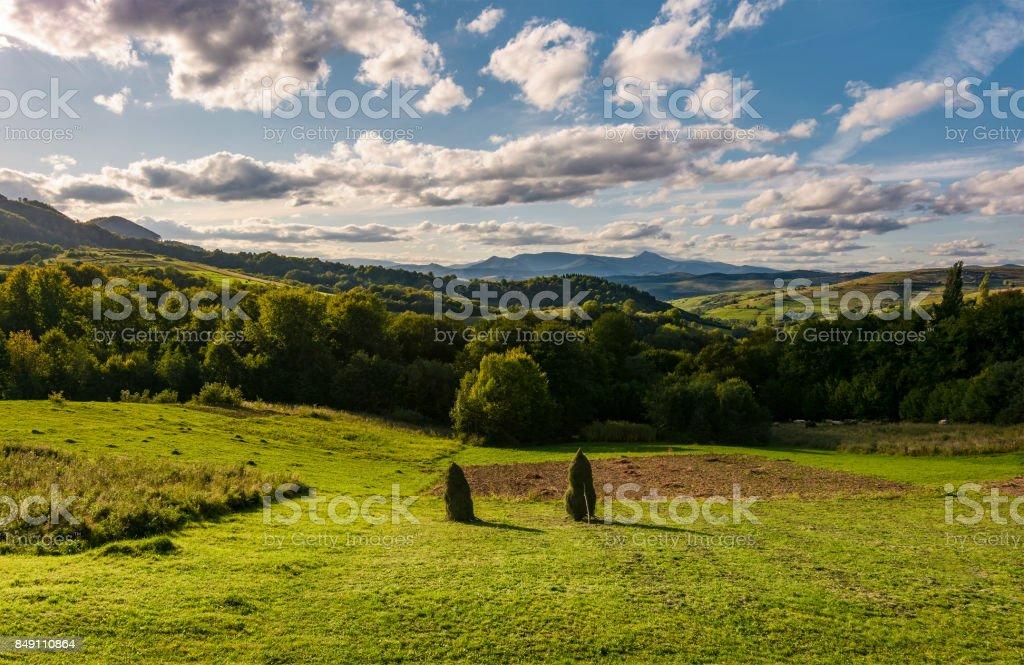 haystack on fields in mountainous rural area stock photo