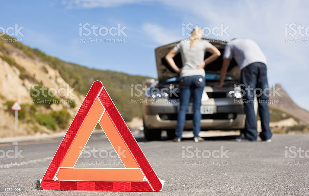 Hazard Sign For Couple with Car Trouble royalty-free stock photo