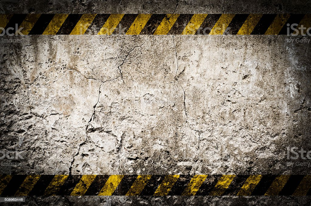 Hazard tape on blank dirty wall stock photo