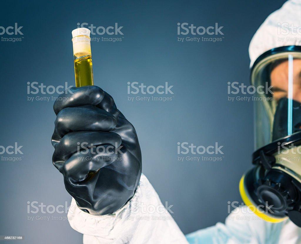 Hazardous Material Protection Suit Worker Showing Test Tube Liquid stock photo