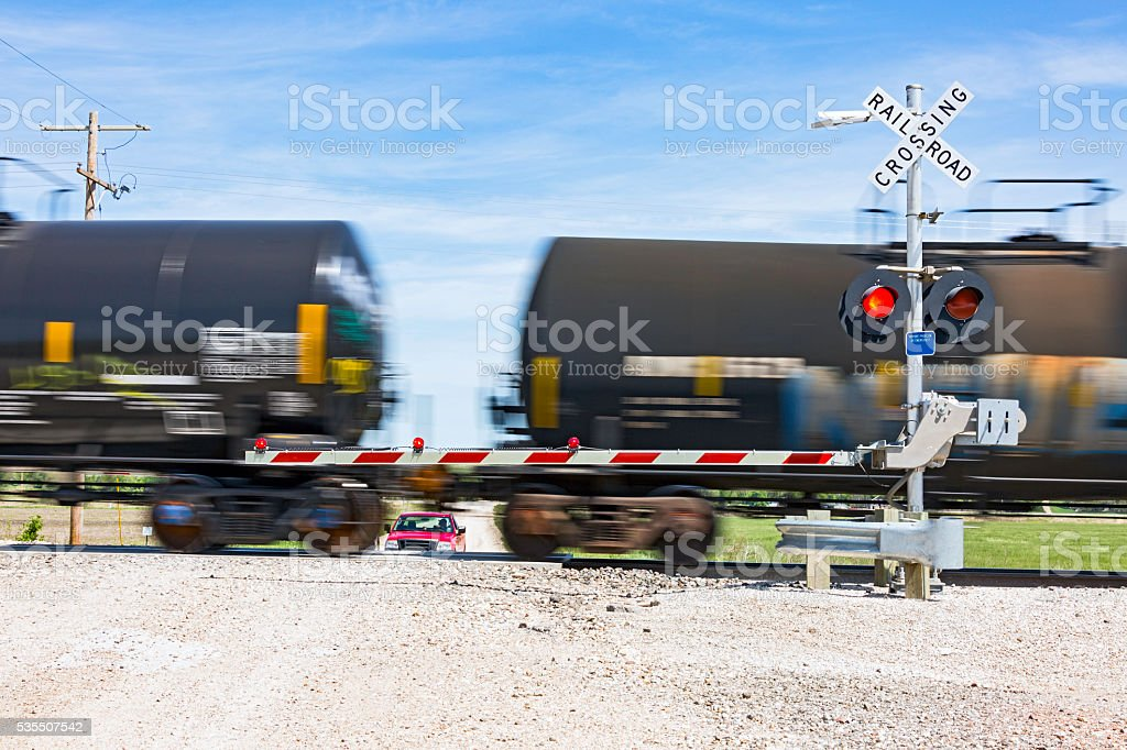 Hazardous rail freight passes crossing on rural road. stock photo