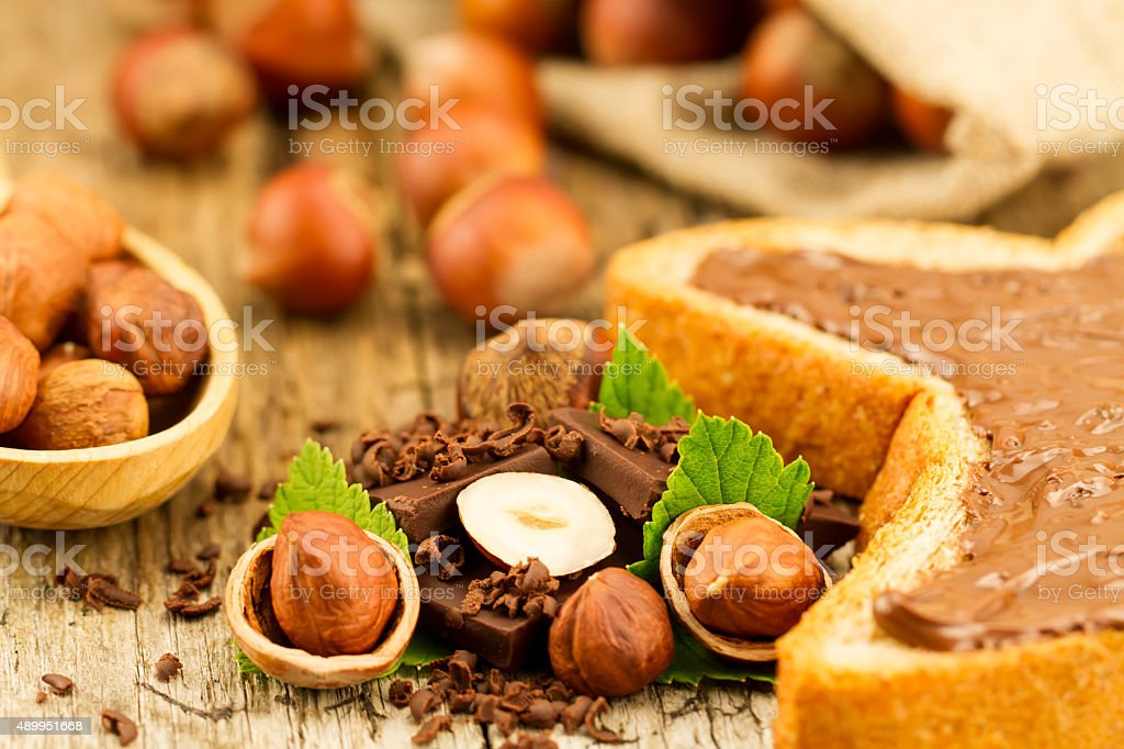 hazelnut with chocolate, toast and green leaves stock photo