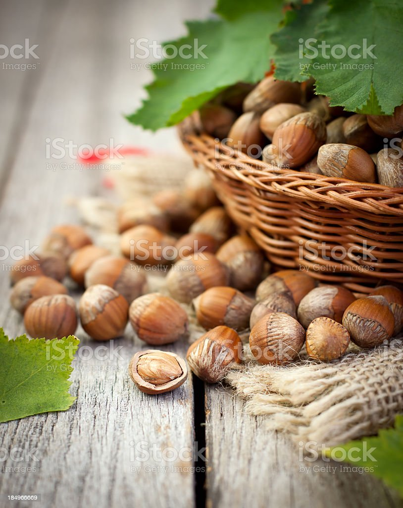 Hazelnuts basket on top of wood table stock photo