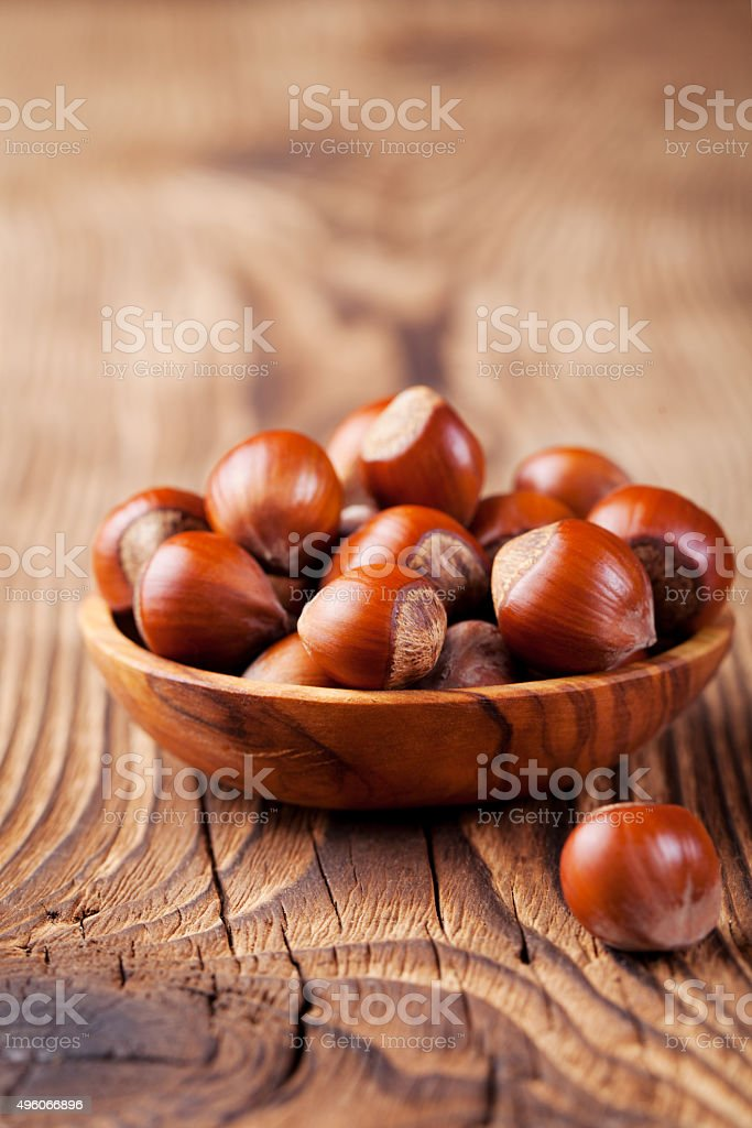 Hazelnuts in a wooden bowl. Wooden background. stock photo