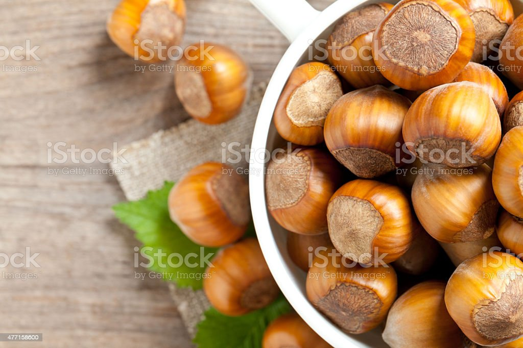 Hazelnuts in bowl on old table stock photo