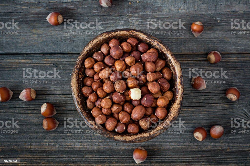 Hazelnuts in bowl on wooden background stock photo
