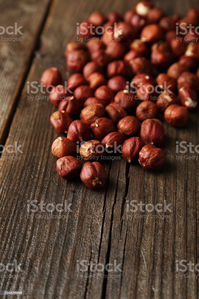 Hazelnuts on brown wooden background stock photo