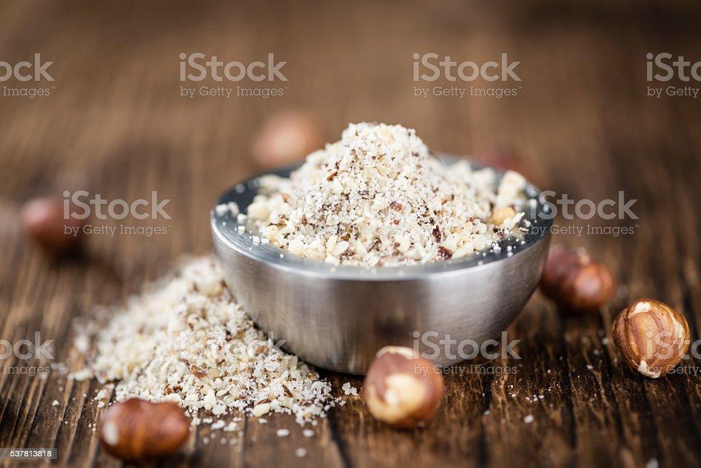 Hazelnuts (grounded) on wooden background stock photo