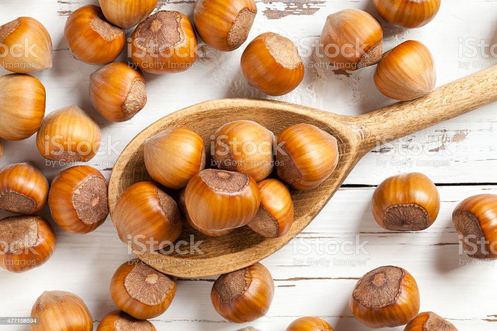 Hazelnuts on wooden spoon stock photo