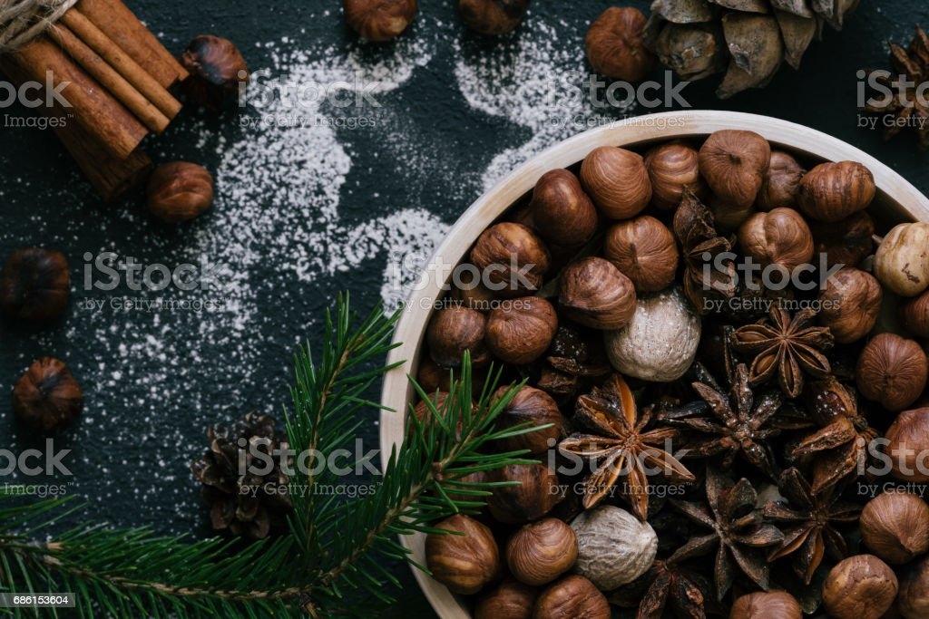 Hazelnuts, star anise, nutmeg in wooden plate, top view stock photo